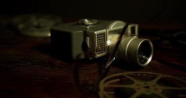 panorâmica no nível da mesa de bobinas de filme, câmera velha e tiras de filme na mesa em 4k