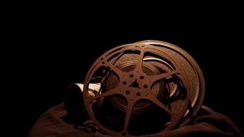 clipe de dois rolos de filme e uma câmera antiga girando com uma iluminação dramática em 4k