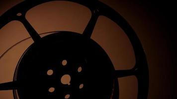 close-up de meio rolo de filme girando com iluminação escura e fundo quente em 4k