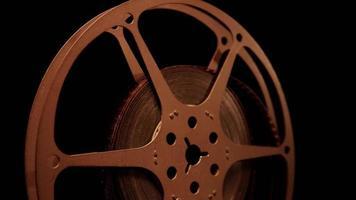 close up da bobina de filme girando com iluminação frontal mostrando reflexos de luz em fundo escuro em 4k