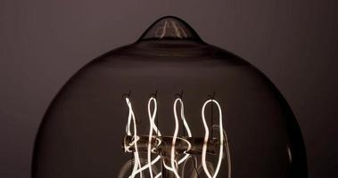 close-up extremo de lâmpada vintage com filamento laranja de primavera brilhando na escuridão em 4k