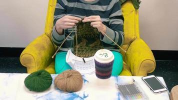 mujer tejiendo mientras está sentado con colores brillantes | material de archivo gratis