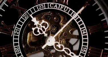 Extreme close up of pocket watch with beautiful clock hands and exposed machinery coming one minute seven seconds in 4K time lapse video