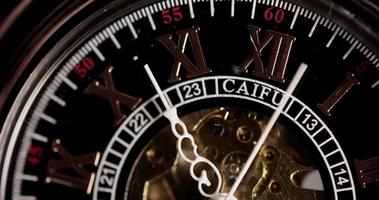 Extreme close up of pocket watch with exposed machinery coming for thirteen minutes in 4K time lapse video