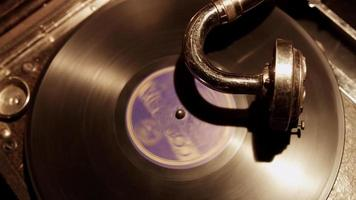 Diagonal traveling shot of vinyl disc with purple label spinning on old classis turntable in 4K