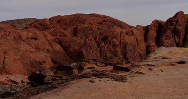Toma panorámica que va a la derecha de las colinas rojas en un paisaje desértico con cielo gris en 4k video