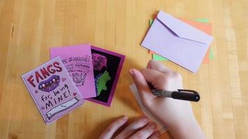 Fotografía cenital de las manos haciendo tarjetas de San Valentín | material de archivo gratis