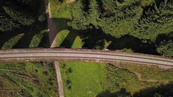 Drone ascendiendo por encima de un viaducto en un bosque