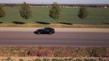 Drone follows a sports car from left profile in 4K