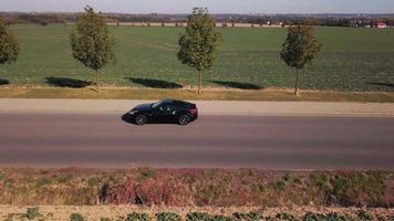 drone suit une voiture de sport du profil gauche en 4k