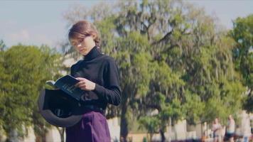 Una foto panorámica de una mujer leyendo un libro azul en el parque.