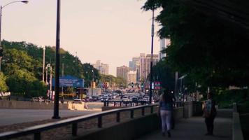 pessoas descansando na calçada com carros e edifícios ao fundo