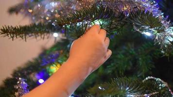 uma criança pendurando um enfeite na árvore de natal video