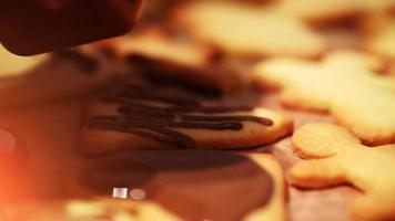 close up de uma garoa de chocolate sobre biscoitos de natal recém-assados