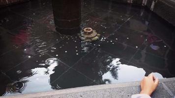 fille jetant une pièce à la fontaine