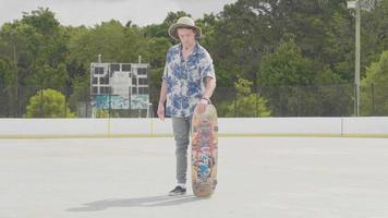 junger Mann mit Hut, der sein Skateboard aufhebt und es dreht