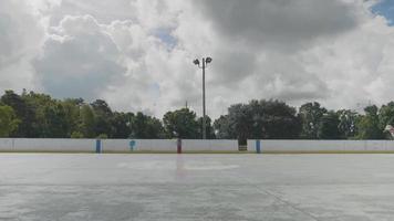 Joven montando su patineta en la pista de patinaje en un día soleado