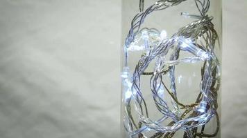 close up de decoração dourada com luzes em frasco de vidro
