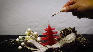 kvinna som tänder ett rött julljus video
