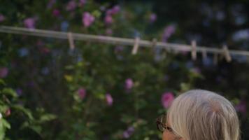 Clip de cámara lenta de anciana tomando pinzas para la ropa