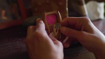 close-up de mãos segurando uma pequena caixa de madeira video