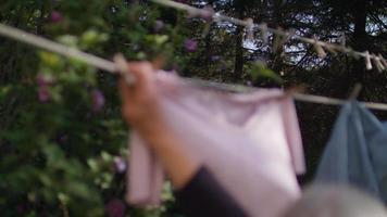 anciana colgando ropa en cámara lenta