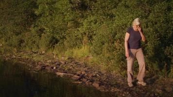 senhora andando perto de um lago com árvores ao fundo video