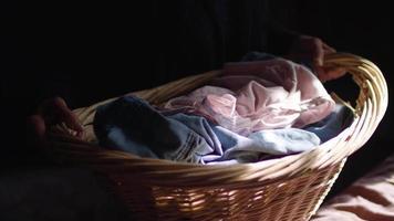 close-up de uma senhora segurando seu cesto de roupa suja video