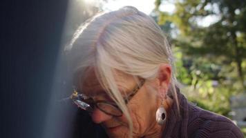 clip palmare di una vecchia signora che raccoglie i vestiti nel suo giardino