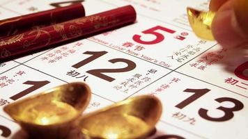 close-up de homem colocando um lingote de ouro chinês no calendário