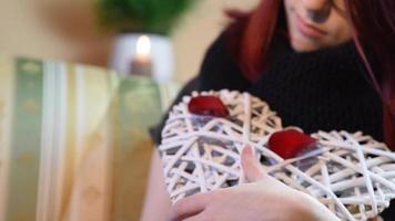 presente de dia dos namorados. jovem segurando um coração de madeira branco com pétalas de rosa