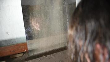 Hombre deprimido y enojado está sentado frente a su reflejo en una vieja casa abandonada