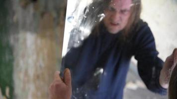Hombre deprimido y enojado sostiene un espejo y lo mira con enojo
