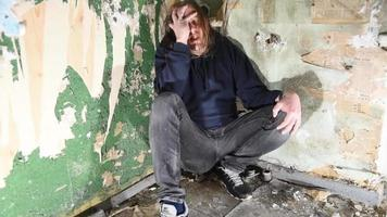 hombre deprimido y enojado está sentado en la esquina de una casa abandonada