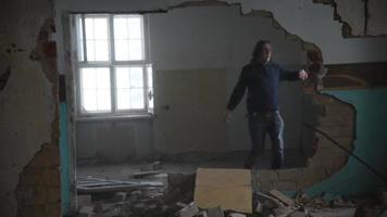 Hombre deprimido y enojado está pateando contra la pared en una casa abandonada