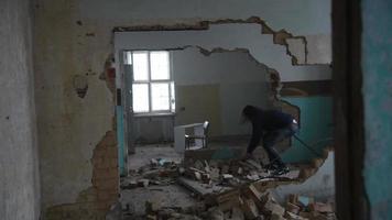 Deprimido y loco arroja piedras en una vieja casa abandonada