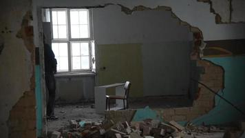 Depressed and mad man throws a chair through a room in an old abandoned house video