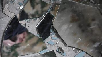 Hombre deprimido y enojado mira en fragmentos de vidrio roto