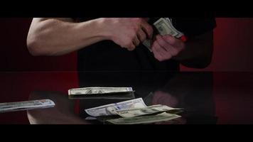 Manos de un hombre recogiendo billetes de $ 100 de una superficie reflectante - dinero 0030