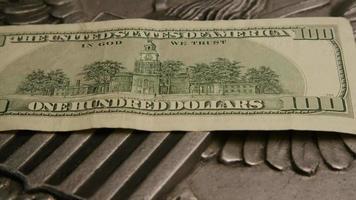 rotação de imagens de estoque de papel-moeda americano em um fundo de escudo de águia americana - dinheiro 0389