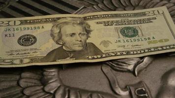 rotação de imagens de estoque de papel-moeda americano em um fundo de escudo de águia americana - dinheiro 0393
