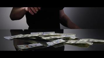 Manos de un hombre recogiendo billetes de $ 100 de una superficie reflectante - dinero 0034
