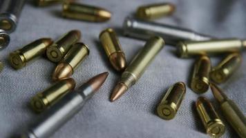 Disparo giratorio cinematográfico de balas sobre una superficie de tela - balas 098