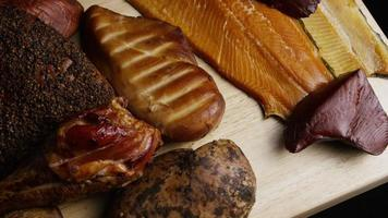 Rotating shot of a variety of delicious, premium smoked meats on a wooden cutting board - FOOD 075