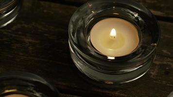 Velas de té con mechas en llamas sobre un fondo de madera - velas 003
