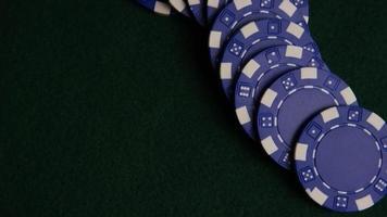 Disparo giratorio de cartas de póquer y fichas de póquer sobre una superficie de fieltro verde - Poker 051