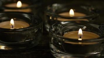 Velas de té con mechas en llamas sobre un fondo de madera - velas 022