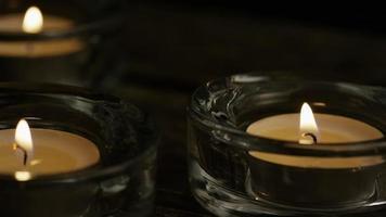 Velas de té con mechas en llamas sobre un fondo de madera - velas 011
