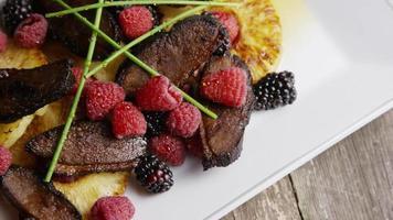 tomada rotativa de um delicioso prato de bacon de pato defumado com abacaxi grelhado, framboesas, amoras e mel - comida 114 video