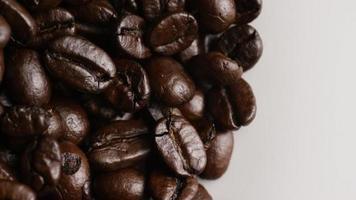 rotierender Schuss von köstlichen, gerösteten Kaffeebohnen auf einer weißen Oberfläche - Kaffeebohnen 061
